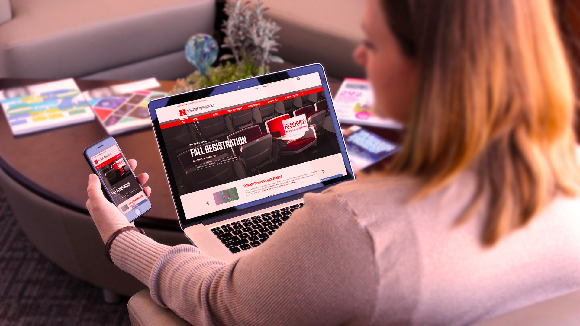 Woman compares the Nebraska website on mobile phone and laptop.